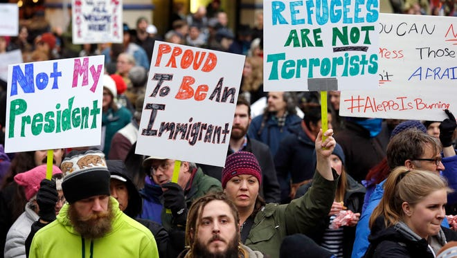 People begin to gather Sunday in downtown Seattle before a rally protesting President Donald Trump's travel ban on refugees and citizens of seven Muslim-majority nations.
