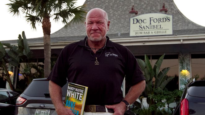 """Sanibel Island resident and author Randy Wayne White stands outside Doc Ford's Rum Bar & Grille restaurant. White held a book signing event for his newest book """"Bone Deep."""""""