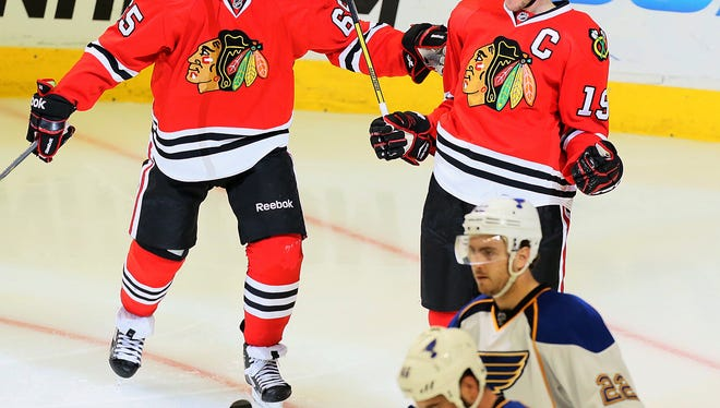 Chicago Blackhawks captain Jonathan Toews (19) reacts after scoring the go-ahead goal on a power play in third-period action during Game 6 of a Western Conference series against the St. Louis Blues on Sunday.  At left is Blackhawks center Andrew Shaw. In the foreground are St. Louis Blues defensemen Kevin Shattenkirk (22) and Roman Polak.