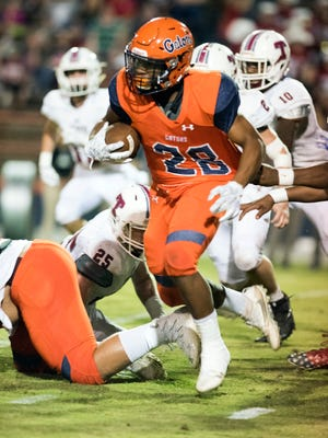 Escambia High, running back Ray Samuel, (No. 28) fight his way through the Tate High defense during the Gators first home game of the season Friday night.