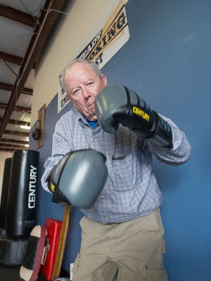 Boxer Sam Crow, of Pensacola Beach, strikes a pose after donning his gloves during the Parkinson's boxing class at Rock Steady Boxing Emerald Coast in Gulf Breeze on Friday, January 12, 2018.