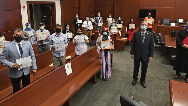 Hailing from nine countries, 17 new U.S. citizens are shown Friday following a citizenship and naturalization ceremony at U.S. District Court in Erie. Presiding over the ceremony were Erie Mayor Joe Schember, center, right, and U.S. Bankruptcy Judge Thomas P. Agresti, far right.