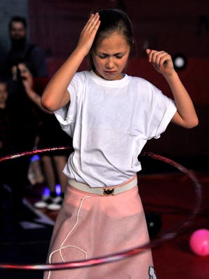 Melody Peyton, 7, taps the side of her head in order to maintain her rhythm during a hula-hoop contest Saturday at the North 10th Street Boys & Girls Club. The Sweetheart Sock Hop was organized by the Abilene Pinup Dolls and benefited the Boys & Girls Club.