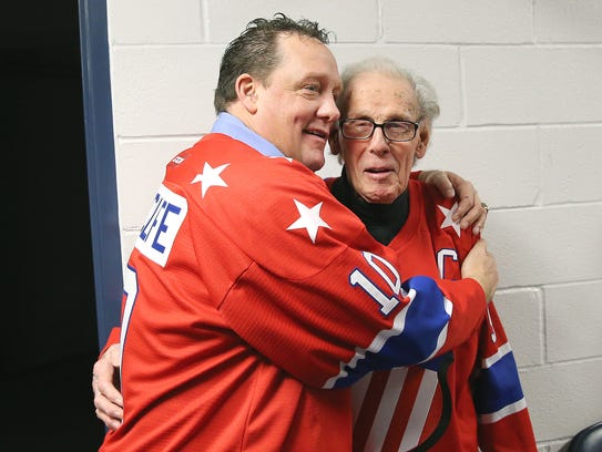 Amerks legend Dick Gamble (right) receives a hug from
