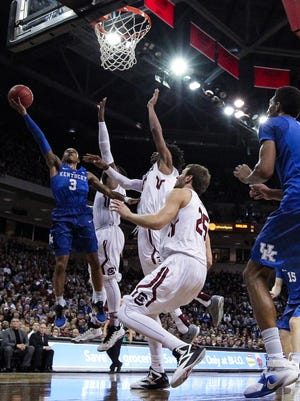 Feb 13, 2016; Columbia, SC, USA; Kentucky Wildcats guard Tyler Ulis (3) shoots a layup against South Carolina Gamecocks forward Mindaugas Kacinas (25) and guard Duane Notice (10) at Colonial Life Arena. Mandatory Credit: Jim Dedmon-USA TODAY Sports