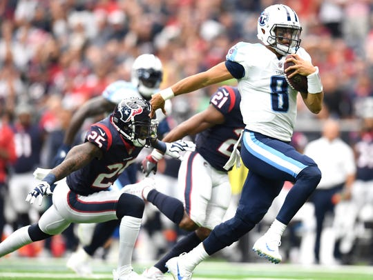 Titans quarterback Marcus Mariota (8) races past defenders