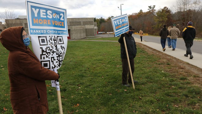 Joan Atlas, of Winchester, and Jeff Sugarman, of Arlington, held signs supporting Question 2 outside Burlington High School on Election Day, Nov. 3, 2020.