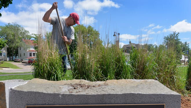 A sign seems to provide the motto as Gray Plant Mooty attorney and volunteer Scott Wick works with ground cover in a landscaped area Thursday, June 16, at Lake George.