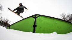 A skier takes off from one of the features in the terrain