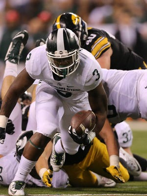 Michigan State Spartans RB LJ Scott runs for a first down against the Iowa Hawkeyes during the second half of the Big Ten Championship on Saturday, December 5, at Lucas Oil Stadium in Indianapolis, Indiana.