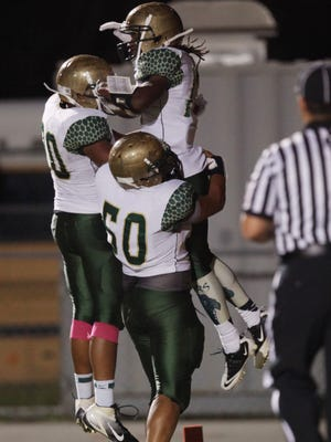 Island Coast's James Washington Peyton Westbrook and Charles Ellis celebrate after a touchdown during a game at Dunbar High on Friday night.