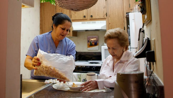 A United Home Care Services home health aide pours cereal for a client.