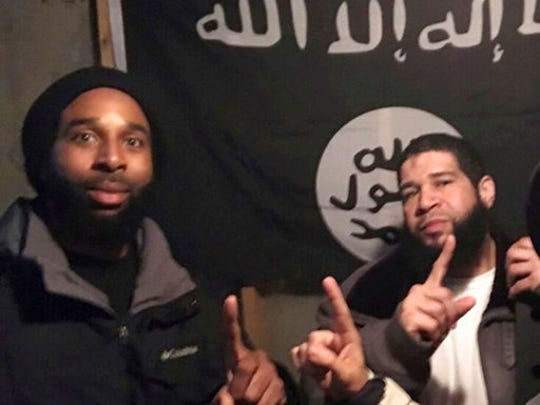 In this undated photo provided by the Federal Bureau of Investigation Joseph D. Jones, left, and Edward Schimenti pose in front of an Islamic State group flag. Jones and Schimenti were arrested by FBI agents on Wednesday, April 12, 2017 on terrorist charges for allegedly conspiring to support the Islamic State militant group.