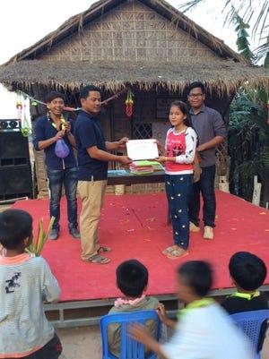 Kao Virak hands an award to a students.