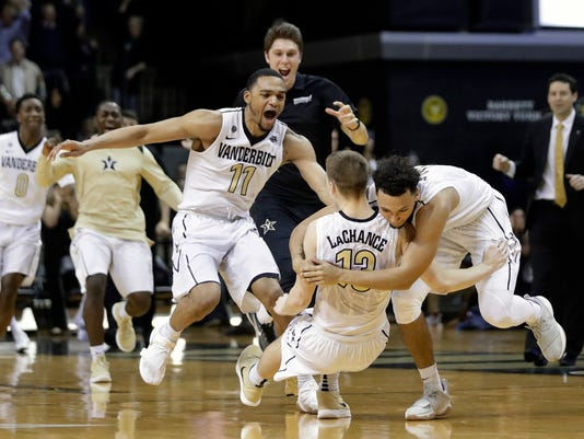 Vanderbilt guard Riley LaChance (13) is mobbed by teammates Jeff Roberson (11) and Payton Willis, right, after LaChance hit the winning 3-point basket against Mississippi State in the final second of the second half of an NCAA college basketball game Wednesday, Feb. 14, 2018, in Nashville, Tenn. Vanderbilt won 81-80. (AP Photo/Mark Humphrey)