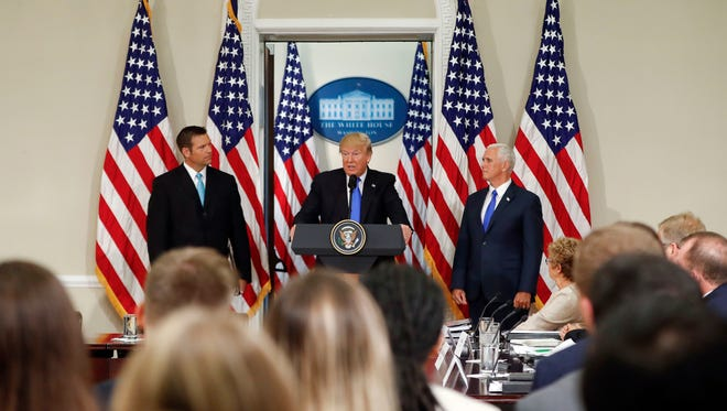 President Donald Trump, with Kansas Secretary of State Kris Kobach, left, and Vice President Mike Pence, right, speaks at a meeting of the Presidential Advisory Commission on Election Integrity in Washington in 2017.