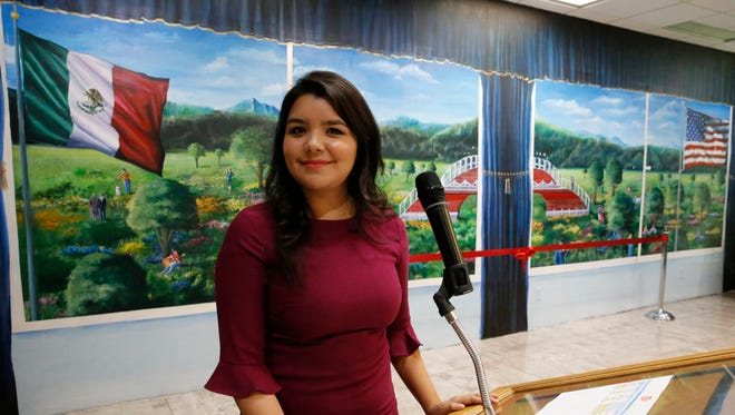 "UTEP student and artist Paloma Vianey Martinez stands in front of her mural titled ""A Bridge Uniting Two Countries,"" that will be displayed inside the Mexican Consulate offices in El Paso. The composition portrays two windows: the left one representing Mexico and the right one the United States."