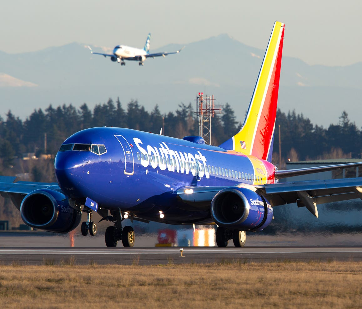 A Southwest Airlines Boeing 737 lands at Seattle-Tacoma International Airport in February 2017 while an Alaska Airlines Embraer E170 shadows it on a nearby runway.