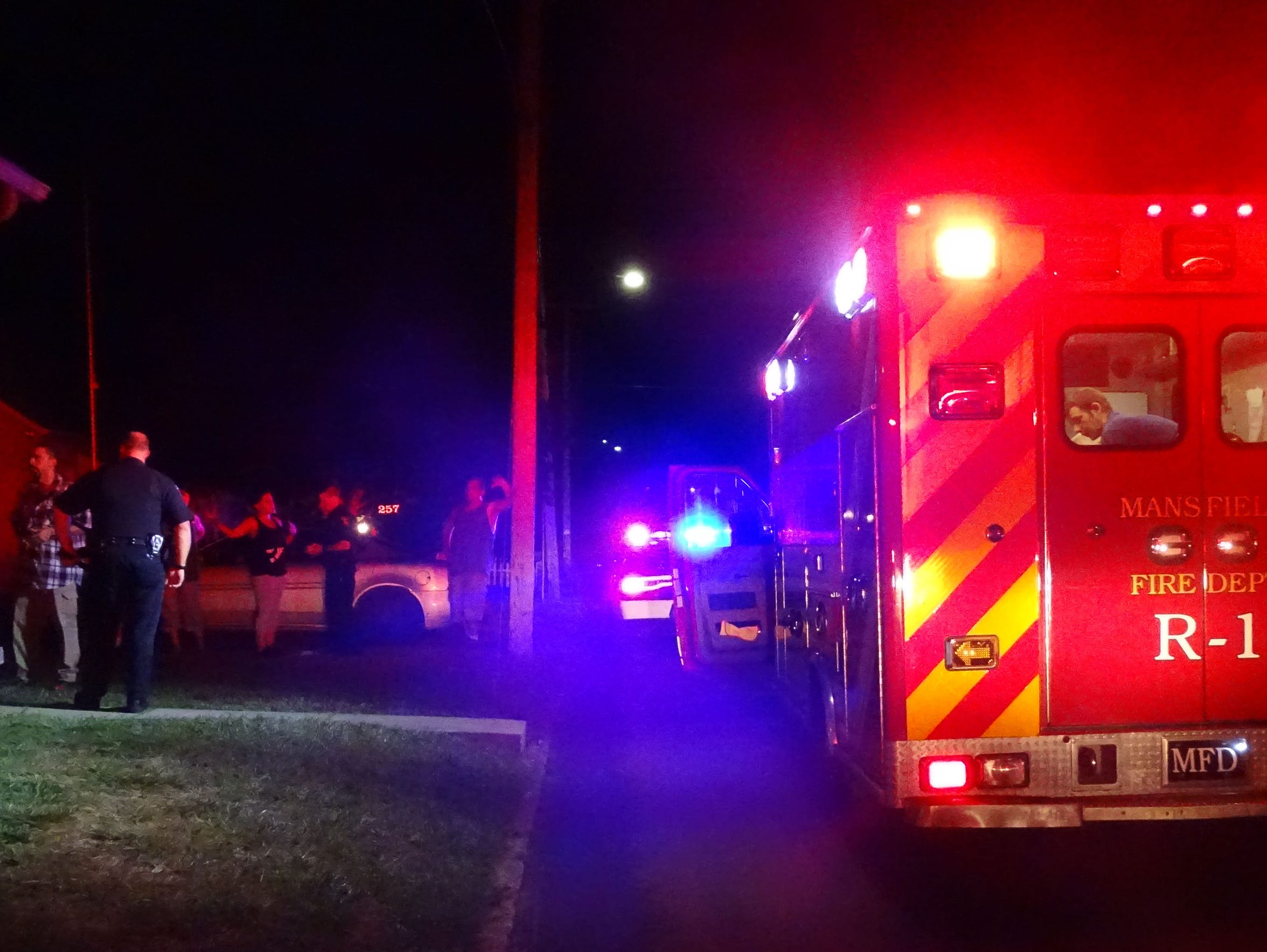 Mansfield police interview witnesses while fire personnel
