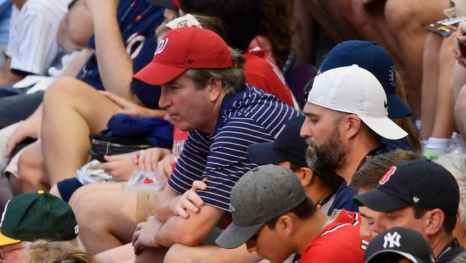 Supreme Court nominee Judge Brett Kavanaugh, in red hat, sits in the stands before the Major League Baseball All-Star Game.