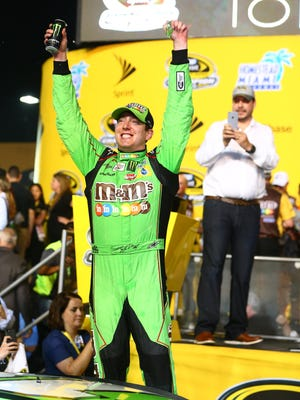Kyle Busch celebrates in after winning the Ford EcoBoost 400 and his first NASCAR Sprint Cup championship.
