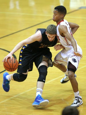 Carmel's Ryan Cline tries to drive through North Central's Wes Stowers in the first half of the game at North Central High School on Friday, Dec. 12, 2014.