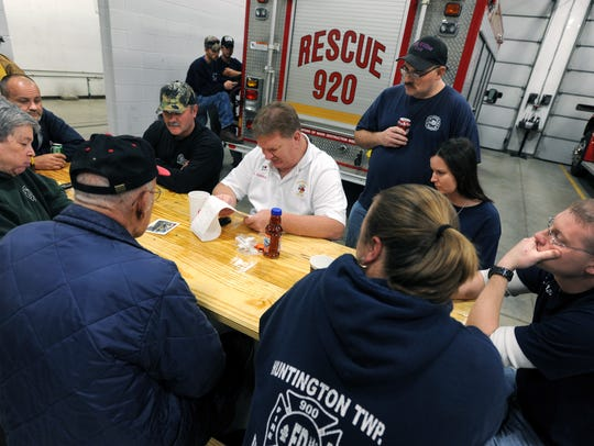 Firefighters and levy supporters listen as Huntington Township Fire Chief Larry Cuckler, center, reads voting results of a 4.8-mill levy that failed in 2013.