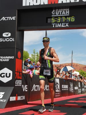 Erik Sorenson crosses the finish line in the 2015 race of the St. George 70.3 Ironman.