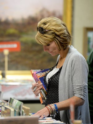 Amy Bray searches for more books during the spring book sale offered by Friends of Morrisson- Reeves Library.