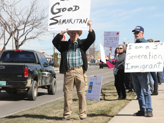 Farmington residents John Carlson, left, and Matt Dodson display signs supporting immigrants during a rally Saturday on the grounds of the Farmington Museum at Gateway Park.