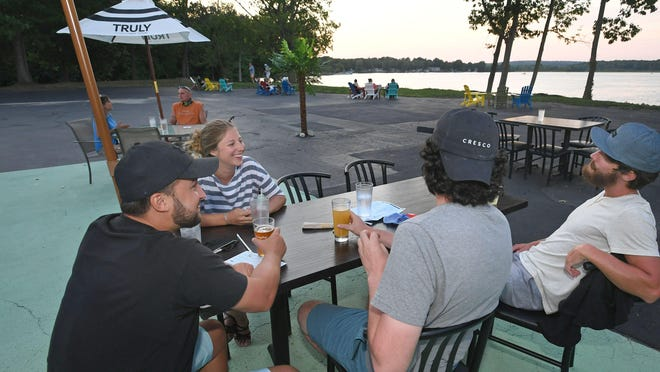 Friends enjoy drinks while taking in the sunset over Edinboro Lake at the Lakeside Beach Bar at Lakeside Commons in Edinboro. From left are Chad Westerburg, 29, of Albion; Allison Kinecki, 24, of Erie; Dan Reagan and Kory Weber, both 29-year-old Edinboro natives. Reagan now lives in Pittsburgh. Weber now lives in Hawaii.