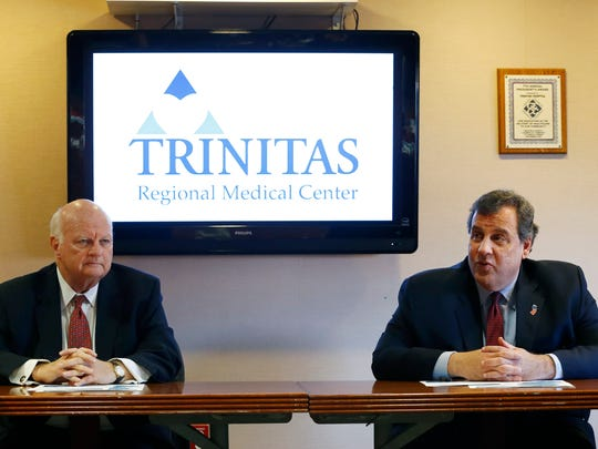 New Jersey Gov. Chris Christie sits with Gary Horan, president and CEO of Trinitas Regional Medical Center, while gathering with hospital board members talking about his proposal of a two-year freeze on property tax liability for the state's nonprofit hospitals while a commission studies the issue.