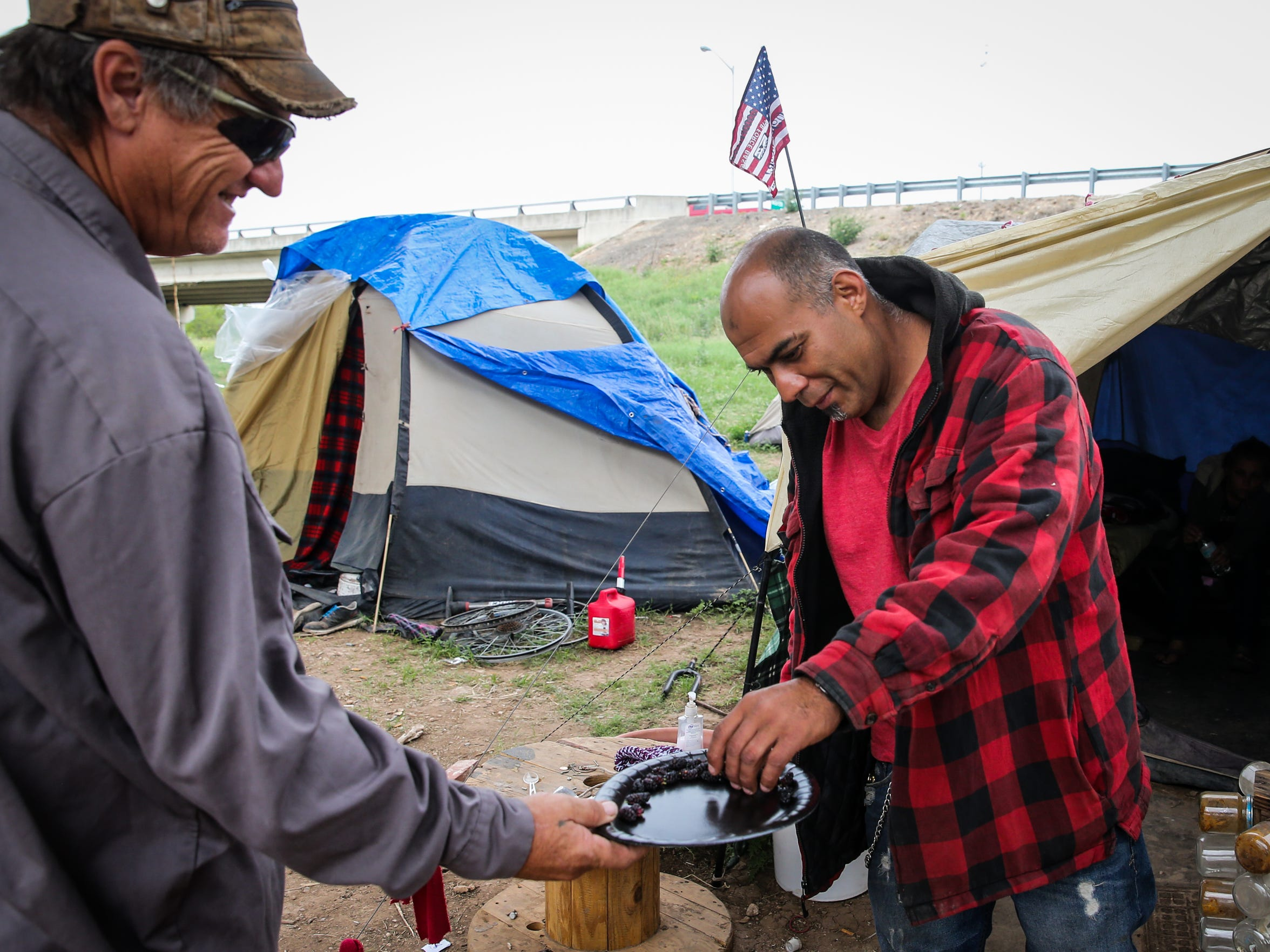 Mike Brannon hands Joe Martinez berries he picked nearby at the tent city under the Houston Harte Expressway in San Angelo last month.