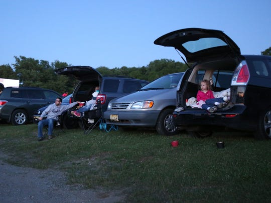 Watching the show from lawn chairs and cars at the Warwick Drive-In Theater June 14, 2014.