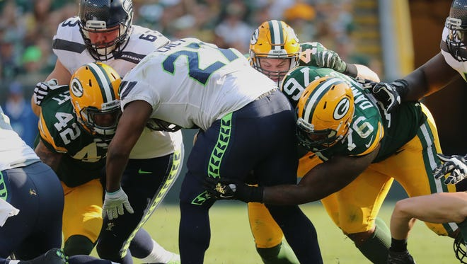 Seahawks running back Eddie Lacy is stopped for no gain by Packers defensive end Mike Daniels (76) and strong safety Morgan Burnett.