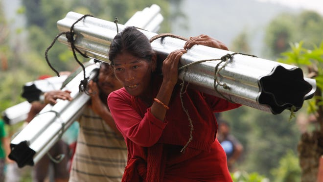 Villagers in the Katunge region carry rolled sheets of tin back to their homes. The tin was donated by Dagsboro mother and daughter Amy and Holly Kaufman and will be used to help rebuild houses damaged by a 7.8-magnitude earthquake April 25, and will provide protection from the elements during the monsoon season.
