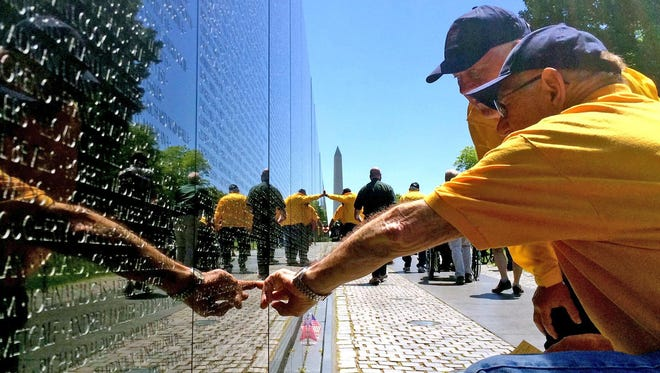 John Brandenburg of Rhinelander touches a name engraved on the Vietnam Veterans Memorial in Washington, D.C., on May 16 on a Never Forgotten Honor Flight while Cal Doering of Gleason looks on.