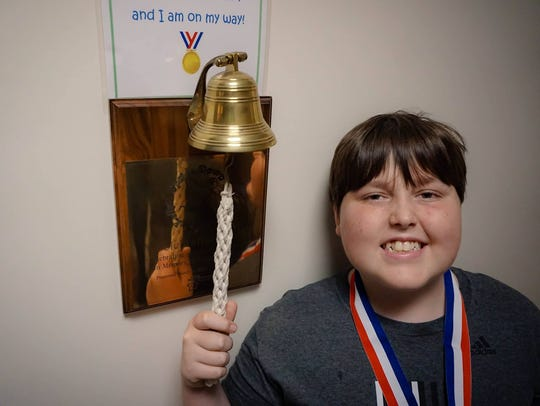 Zane Davidson, 13, rings the bell to signify he is