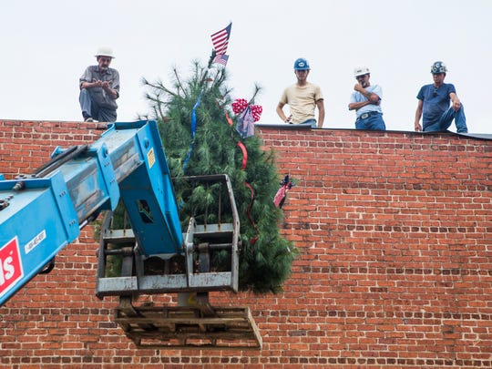 Construction workers lift a ceremonial pine tree onto