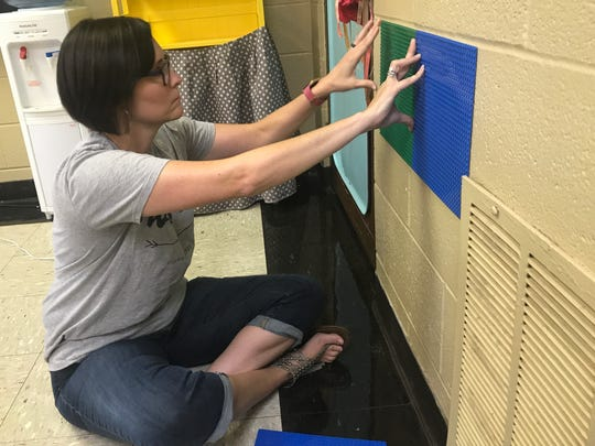 Lyndsey Steffek, a second-grade teacher at Abilene Christian School, glues a LEGO board to the wall of her classroom to create a makerspace for her young students, who return to class Thursday, Aug. 17.
