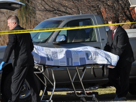 Mortuary personnel remove the body of a victim from a home on 600 South in St. George where two women were found slain Dec. 11, 2010.