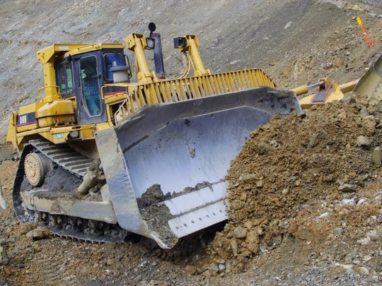 A bulldozer moves earth at the site of a rock slide