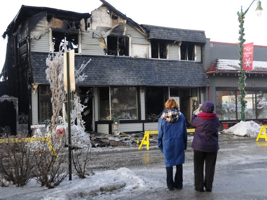 Two women look at the damage to buildings housing Newport