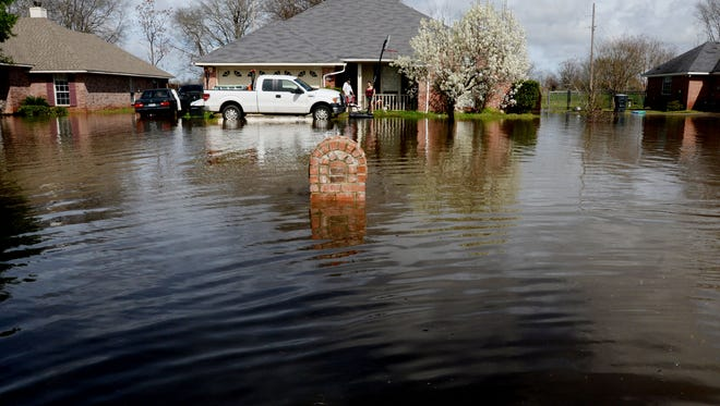 Residents stand in their front porch in the flooded Golden Meadows subdivision in Bossier Thursday afternoon.