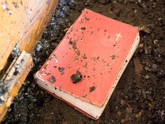 Chunks of charred wood and this hymnal litter the balcony.