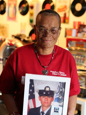 Roxanne Watson, a recipient of a heart transplant, holds a photo of her donor, Michael Bovill, in her Nanuet home. Watson wants to raise awareness to heart health.