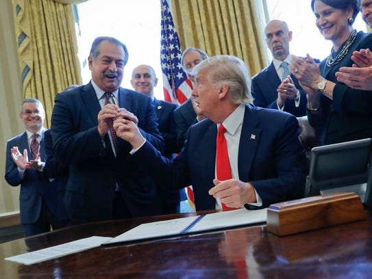 President Donald Trump gives the pen he used to sign