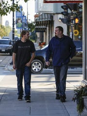 Dustin McCollum, left, and his older brother Jeremy McCollum walk down the sidewalk Wednesday in Manitowoc.