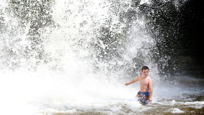 Logan Wheeler, 7, of Beaver Dam, gets lost in the waterfall's thunderous downpour at Eagles Cliff Falls in Montour Falls.