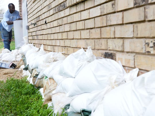 Emmett Wallace puts sandbags around the outside of his sisters house in the Allendale neighborhood of Shreveport in hopes the water will stay out Saturday afternoon.